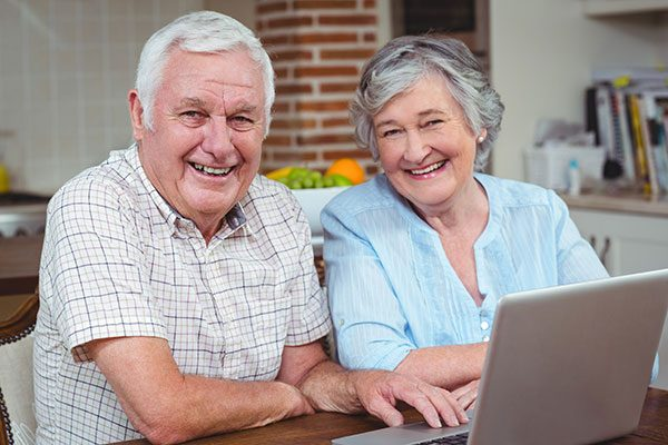 Senior couple making online payment on their HVAC invoice