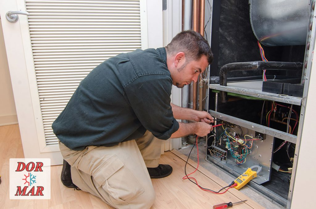 Dor-Mar HVAC technician performing a fall furnace tune-up in Columbus customer's home