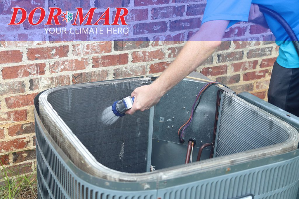 Dor-Mar service technician cleans inside and outdoor AC condenser unit